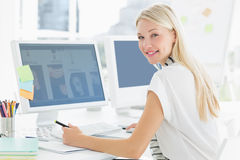 Casual young woman using computer in office Royalty Free Stock Photography