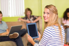 Casual young woman using digital tablet in office Royalty Free Stock Photography