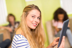 Casual young woman using digital tablet in office. Side view of casual young women using digital tablet in office Royalty Free Stock Photo