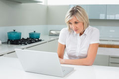 Casual young woman using laptop in kitchen. Casual young woman using laptop in the kitchen at home Stock Photo