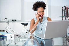 Casual young woman using telephone and laptop Royalty Free Stock Photography