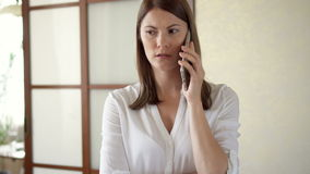 Casual young woman in white blouse standing in living room talking on phone receiving bad news upset stock footage