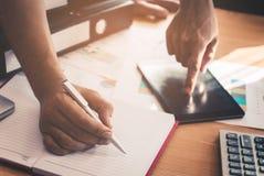 Casuale inizi sulla nota di scrittura dell'uomo di affari dai dati su carta e sulla compressa nella riunione immagine stock