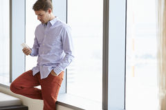 Casually Dressed Businessman Using Mobile Phone In Office Stock Photo