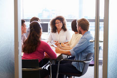 Casually dressed colleagues talking in a meeting room Stock Photography
