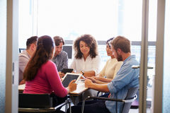 Casually dressed colleagues talking in a meeting room Royalty Free Stock Image