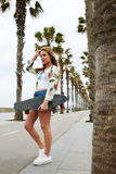 Casually-dressed female hipster with beautiful figure posing with longboard in summer Royalty Free Stock Photography