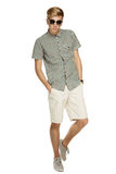 Casually dressed man in full length. Young handsome male in shorts and sunglasses posing in full length with hands in pockets, over white background Stock Photo