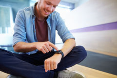 Casually dressed man sits cross legged pointing at his watch Stock Photography