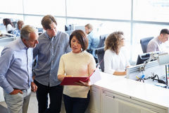 Casually dressed staff standing in a busy open plan office Royalty Free Stock Photos