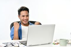 Startup business man raising his hands feeling happy for achieving work while using laptop. Casually-dressed startup business man raising his hands feeling happy stock image