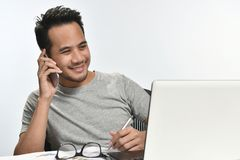 Startup business man smiling while talking on the phone and having fun at work. Casually-dressed startup business man smiling while talking on the phone and Royalty Free Stock Photo