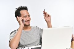 Startup business man smiling while talking on the phone and having fun at work. Casually-dressed startup business man smiling while talking on the phone and Stock Photography