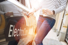 Casually dressed woman opening a vehicle door Stock Image