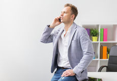 Casually dressed young businessman talking on phone in office Royalty Free Stock Image