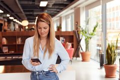 Free Casually Dressed Young Businesswoman Checking Mobile Phone In Modern Open Plan Workplace Royalty Free Stock Photography - 163723117