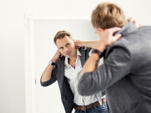 Casually dressed young handsome man in front of mirror. White frame mirror, white background royalty free stock image