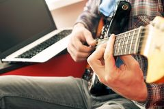 Casually dressed young man with guitar playing songs in the room at home. Online guitar lessons concept. Male guitarist practicing. Young man, hipster folk Royalty Free Stock Photography