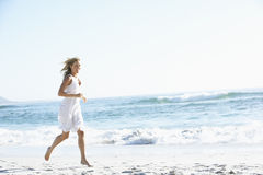 Casually Dressed  Young Woman Running Along Beach Royalty Free Stock Image