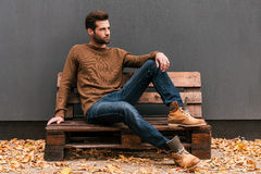 Casually handsome. Handsome young man sitting on the wooden pallet and looking away with grey wall in the background and orange fallen leaves on the floor royalty free stock image