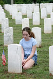 Casualties of War. A young girl mourning a fallen soldier in a graveyard Stock Photography