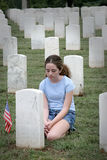 Casualties of War 2. A young girl mourning a fallen soldier in a graveyard (vignette to place emphasis on girl Stock Photo