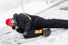 Casualty man is lying on a icy way and calling the ambulance Stock Photography