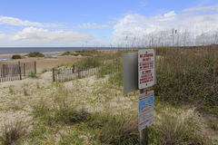 Caswell Beach Dunes Warning Signs. Caswell Beach, NC, USA - September 27, 2015: View of the Atlantic Ocean coast beach with dunes and warning signs about no royalty free stock images