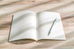 Catálogo en blanco, revistas, mofa del libro para arriba con la pluma en el backgroun de madera Foto de archivo libre de regalías