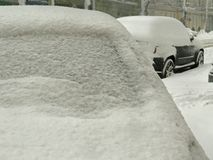 Catástrofes naturais nublado inverno, blizzard, estradas paralizadas nevadas fortes do carro da cidade, colapso Ciclone coberto d fotos de stock
