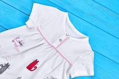 Cat cartoon cotton dress for baby-girl. White organic patterned dress for newborn, blue wooden background. Fancy design infant girl summer outfit stock photo