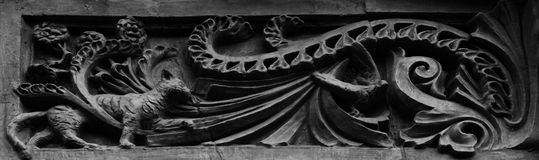Cat chasing bird. Shot in black and white. Placed on the main door of this historic building, sculpture representing a cat and a bird. Set in Paris, France Royalty Free Stock Photos