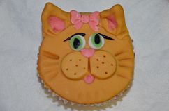 Cat cupcake. Delicious cupcake covered with cat character head with pink ribbon Stock Image