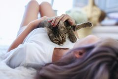 The cat in the embrace of the woman lying on the wool carpet. Young Female lying in bed and holding her beautiful cat. Beautiful royalty free stock image
