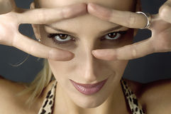 Cat eyes. Blond girl with clear beautiful eyes looking through the fingers Stock Photography