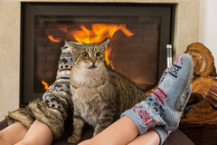 Cat and feet in front of the fireplace Royalty Free Stock Photos