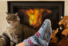 Cat and feet in front of the fireplace Stock Images