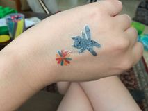 A cat and a flower tatto. Temporary tattoo cat royalty free stock image