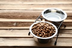 Cat food and water. In bowls on wooden table royalty free stock images