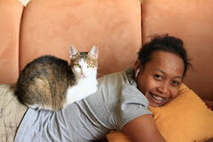 Cat on girl. Tabby and white cat lying on back of indonesian girl - young woman having rest Stock Image