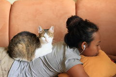 Cat on girl. Tabby and white cat lying on back of indonesian girl - young woman having rest Royalty Free Stock Photos