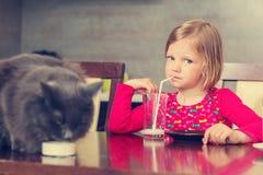 Cat and little girl drinking milk. Stock Photos