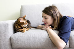 Cat and woman in the living room on the couch. A Cat in the living room on the couch Stock Images