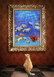 Cat looking at a portrait of a udewater picture  in a golden fra Royalty Free Stock Images