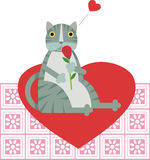 Cat in Love. A gray cat is holding a red rose and sitting on a heart Stock Photo