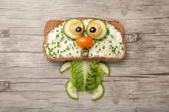 Cat made of bread and vegetables. On wooden board stock photography