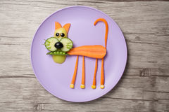 Cat made of raw vegetables on plate and desk royalty free stock images