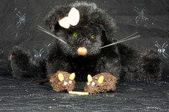 Cat and Mouse. Two cake mice nibbling at a piece of cheese with a black cat lurking behind Royalty Free Stock Photography