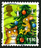 Cat and Mouse UK Christmas Stamp. GREAT BRITAIN - CIRCA 1990s: A used festive postage stamp from the UK, depicting an illustration of a cat and a mouse Royalty Free Stock Photos