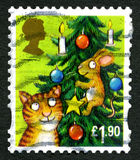 Cat and Mouse UK Christmas Stamp. GREAT BRITAIN - CIRCA 1990s: A used festive postage stamp from the UK, depicting an illustration of a cat and a mouse Royalty Free Stock Image